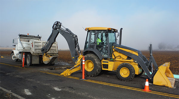 Photograph of heavy equipment working in roadway.